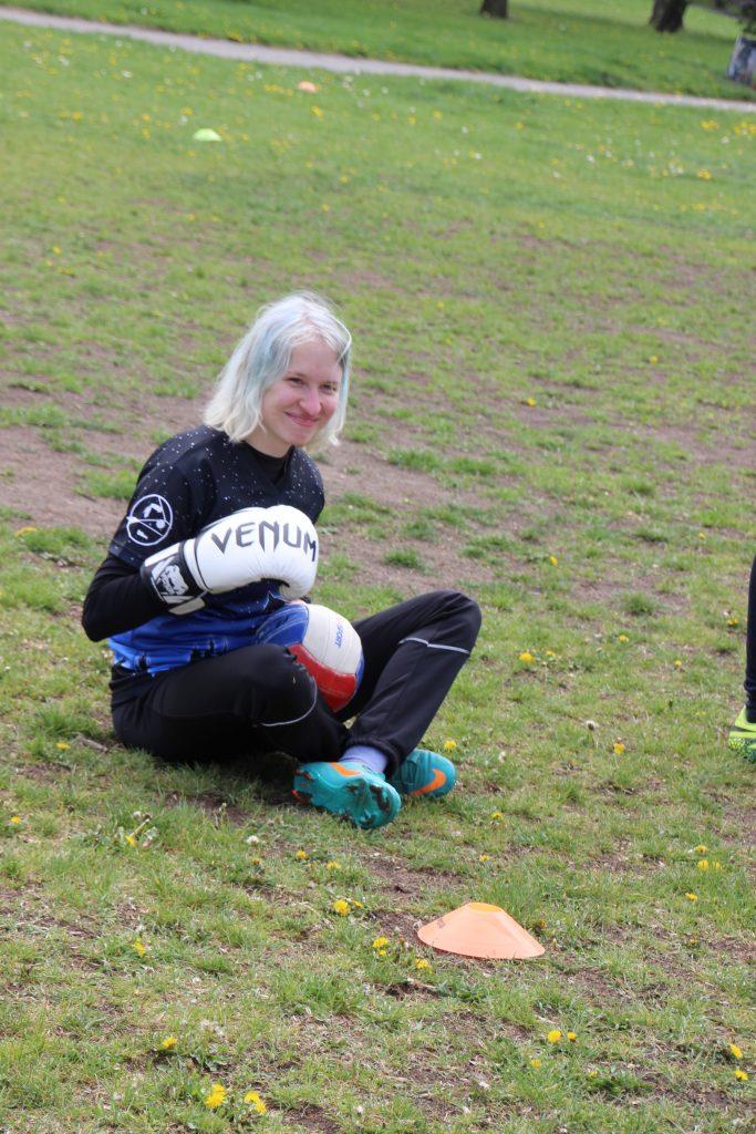 Rodinný den a famfrpál: Dívka (já) s vybdledlými modrými vlasy, v černomodrém pegasím dresu a s boxerskými rukavicemi sedí na trávě.
